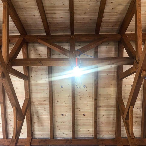 Timber framing in a houses great room.  View of the heavy timbers supporting the roof.