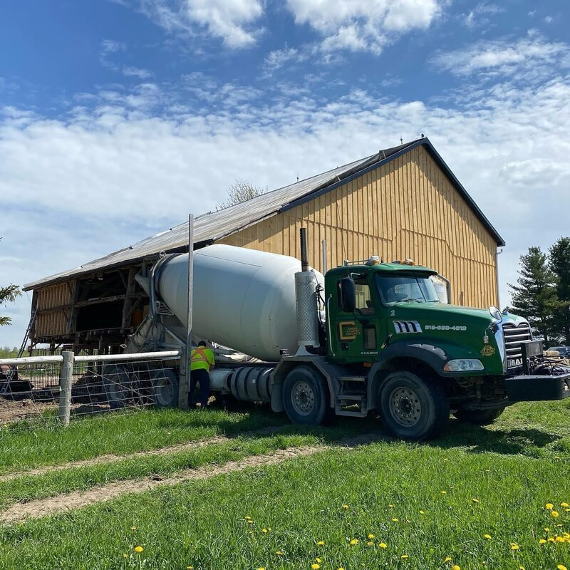 Cement truck in front of a timber barn under construction.