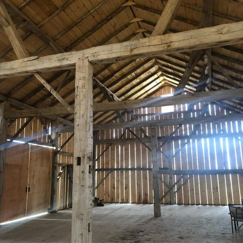 Timber frame barn relocation.  Interior view of the wall and roof framing.  New barn boards with reclaimed timber.