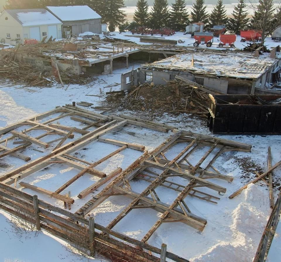 Timer frame barn being relocated.  Timber frames have been placed on the snow covered ground